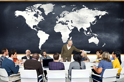 training in front of world map chalkboard - blog